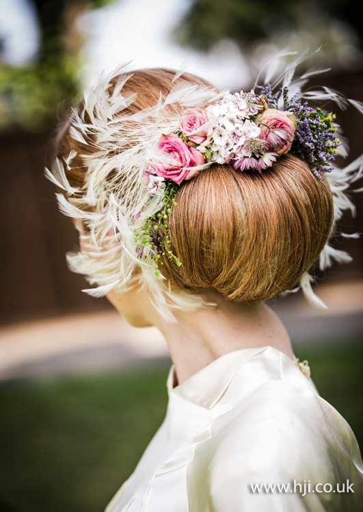 2015 bridal low bun with feathers and flowers