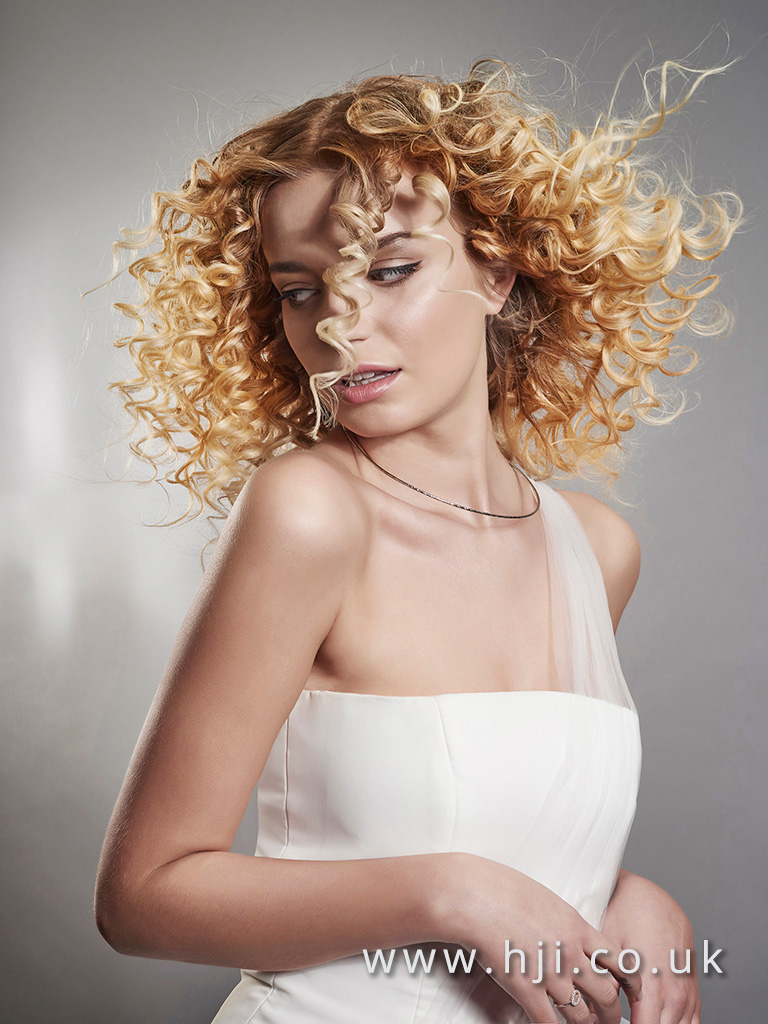 2016 Warm blonde tight corkscrew curl with defined texture and high shine finish