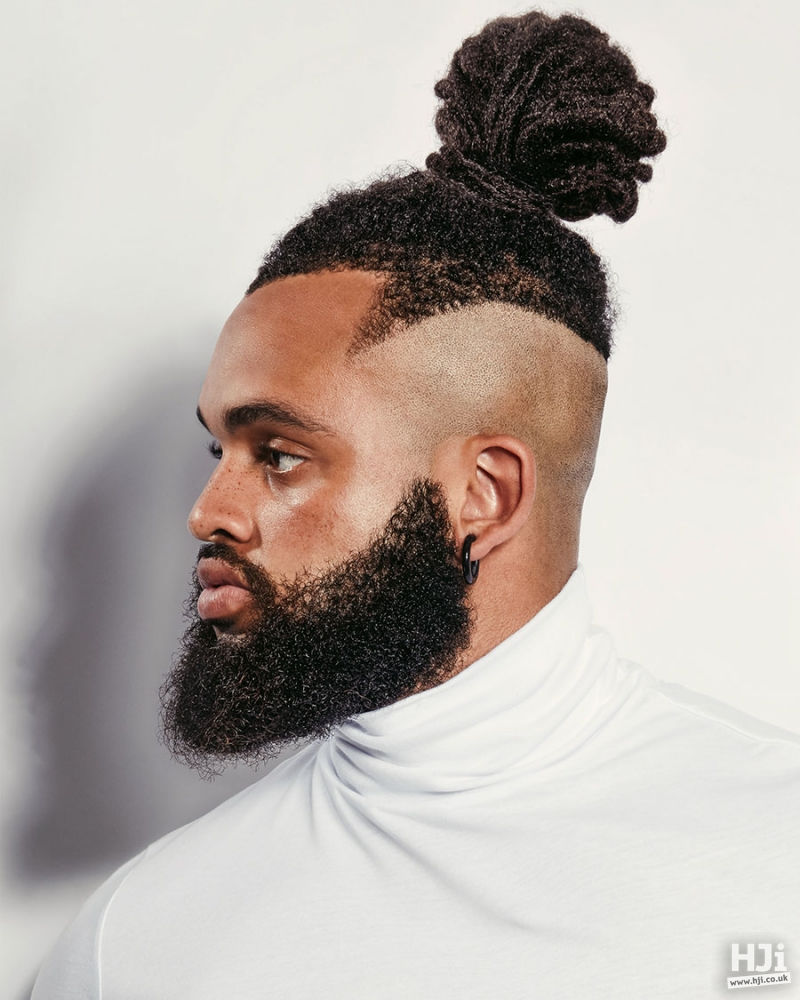 Men's afro geometrical hairstyle put together in a top knot