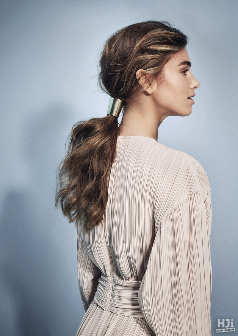 Low ponytail in mid-length wavy brunette
