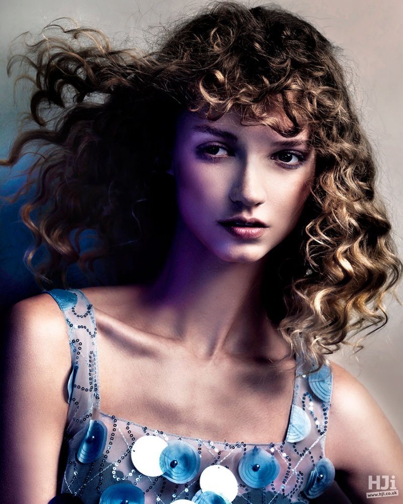 Curly brunette hairstyle with highlights and short fringe