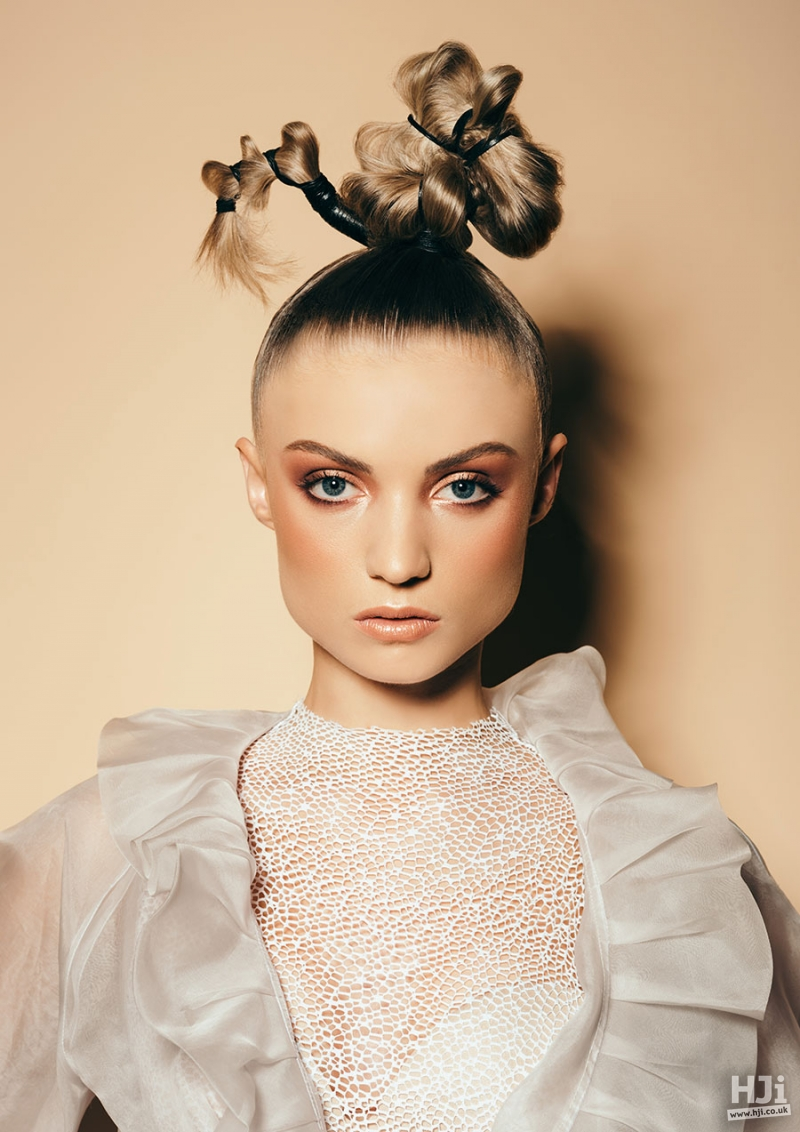 Sleek hairstyle pushed up in an avant garde high ponytail