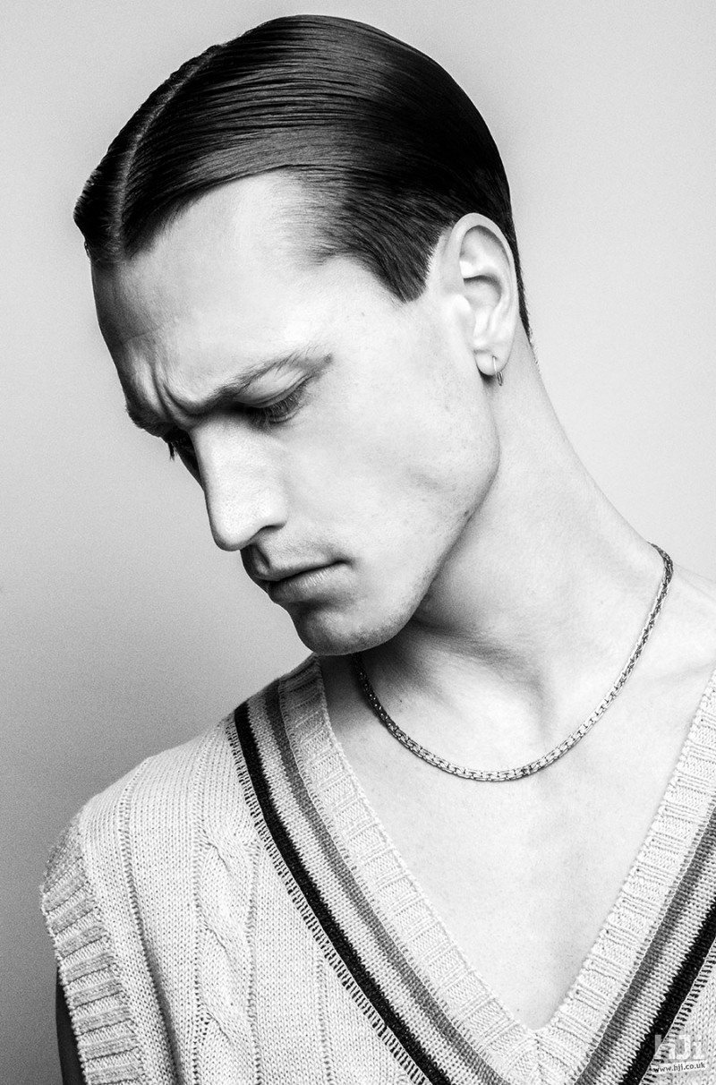 Short sleek men's hairstyle with centre parting