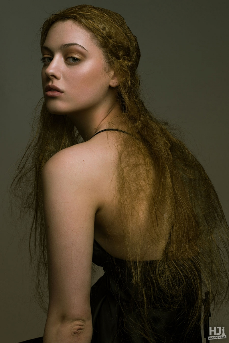 Natural textured long brunette hair styled with a elegant plait