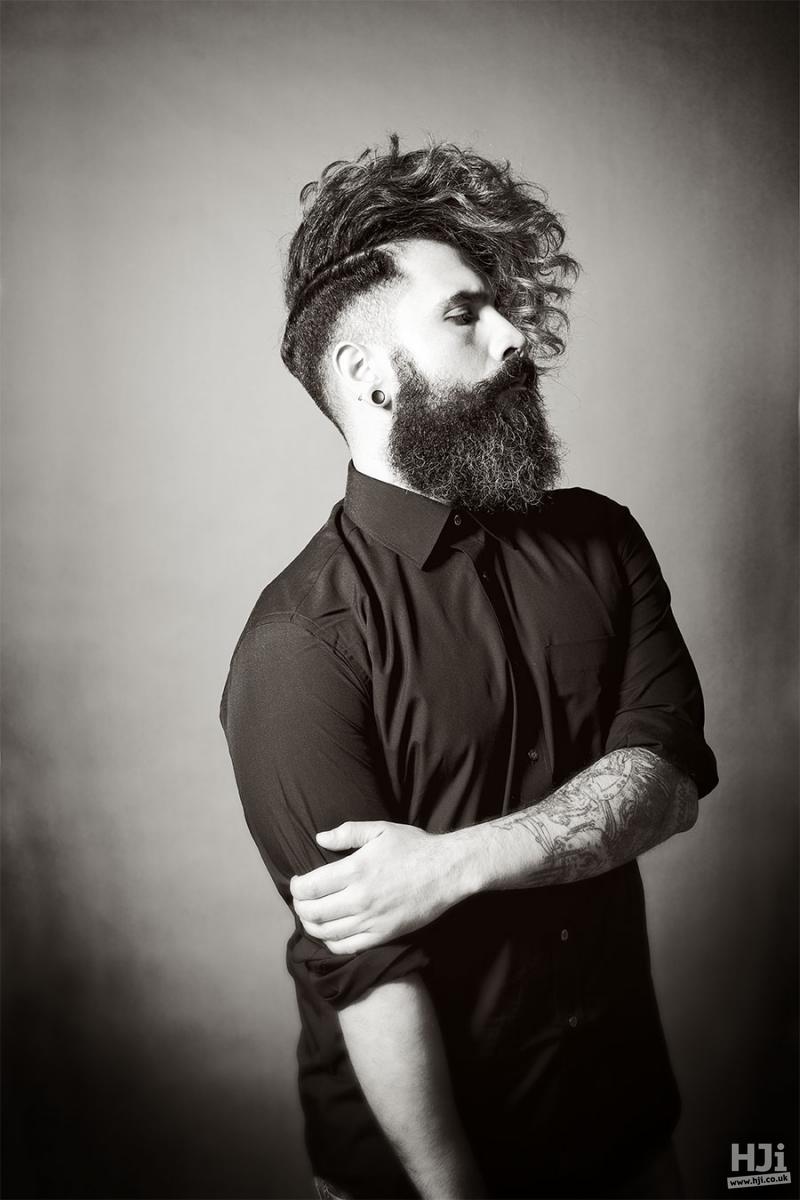 Half-curly, half-sleek editorial men haircut with deep side parting