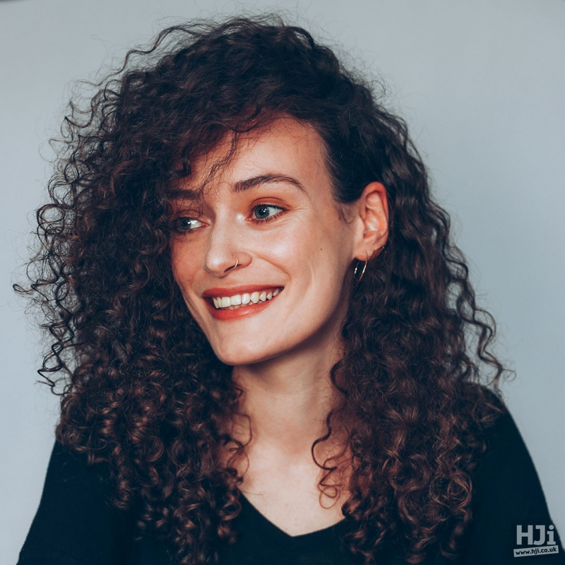 Mid-length curly hairstyle with side parting
