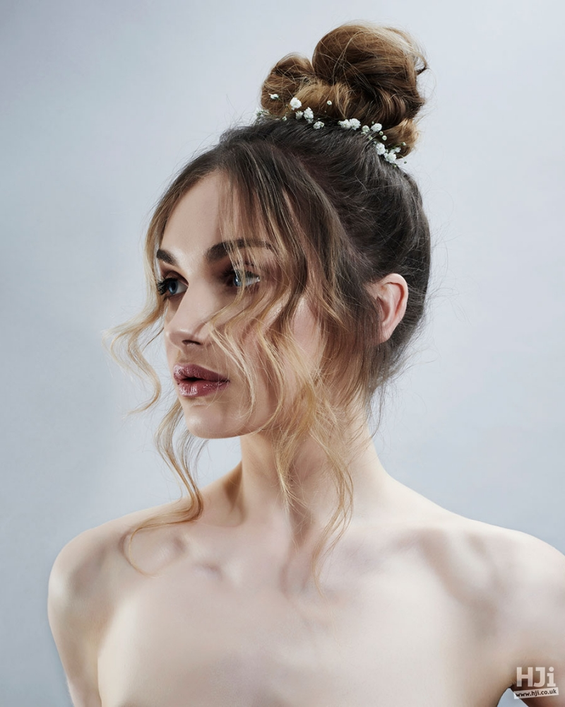 Brunette top knots bridal hairstyle with flowers