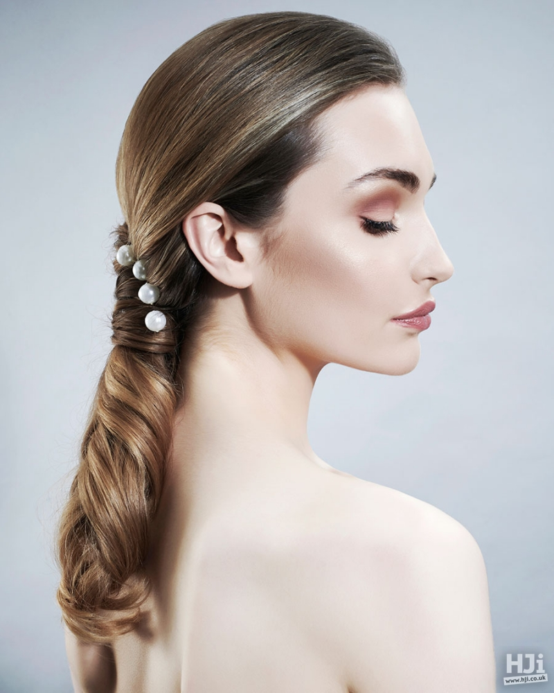 Brunett sleek low ponytail bridal hairstyle with pearls