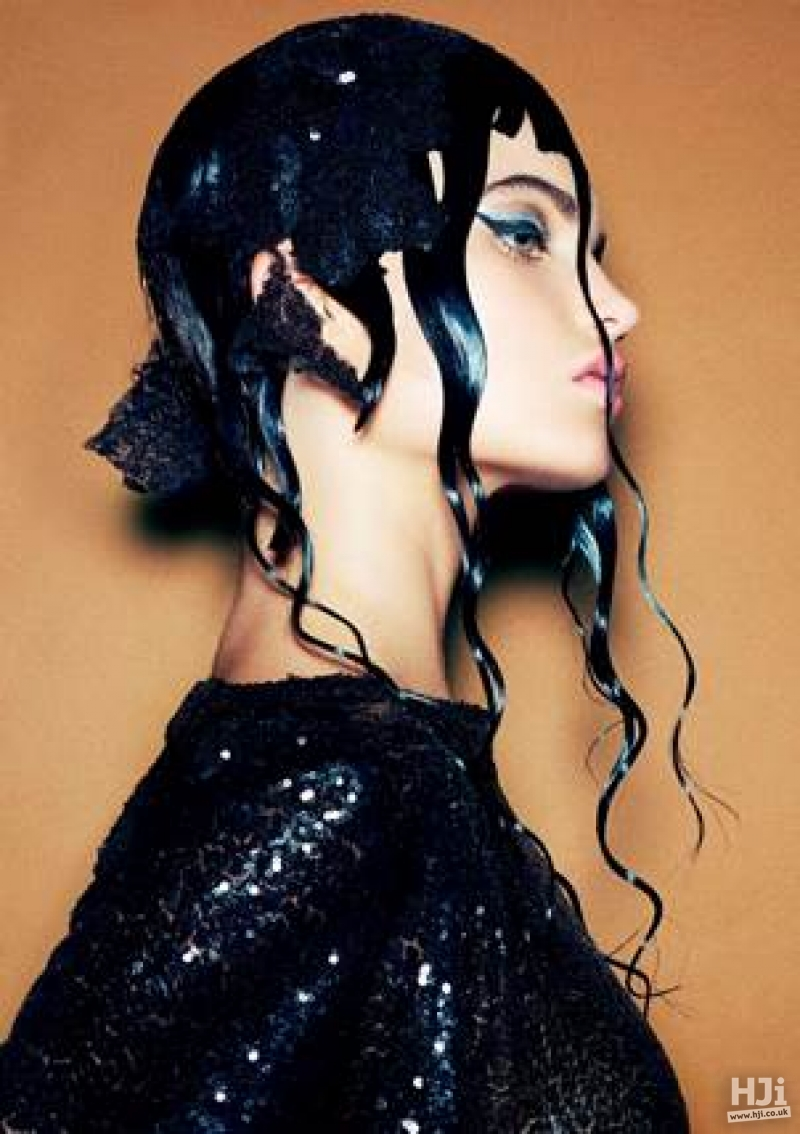 Sleek and wet look black updo with short fringe and waves