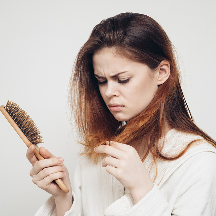 woman looking at comb clients hair loss