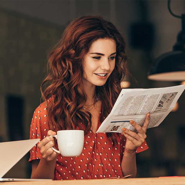 woman reading newspaper about salon local press